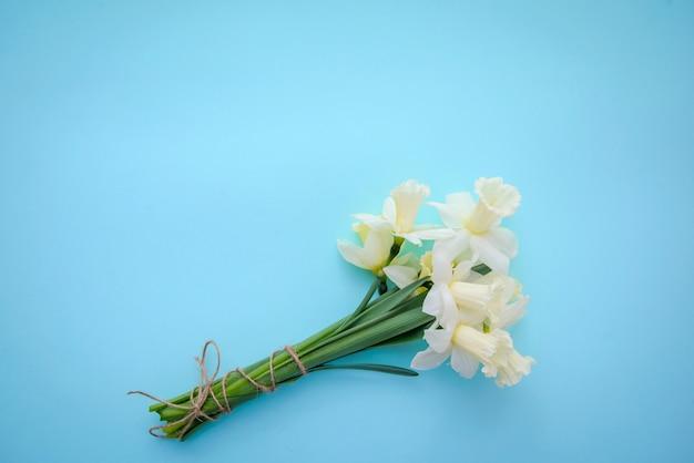 青の背景に白の水仙と薄黄色の花束