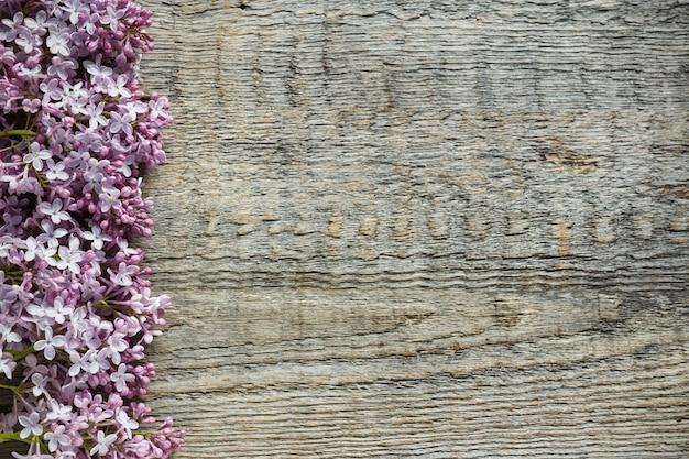 木製の背景にライラック色の花の花束。スペースをコピーします。