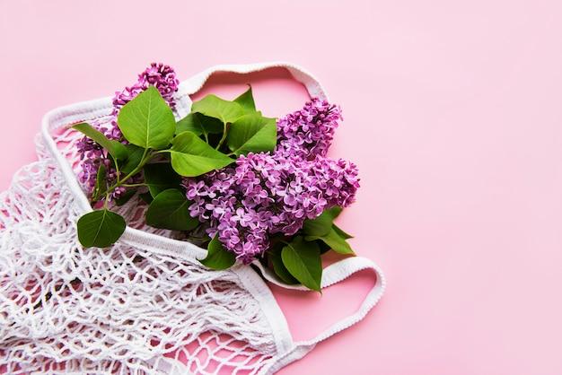 재사용 가능한 쇼핑 에코 메쉬 가방에 라일락 꽃다발. 개념 플라스틱, 폐기물 제로. 공간 복사 평면도