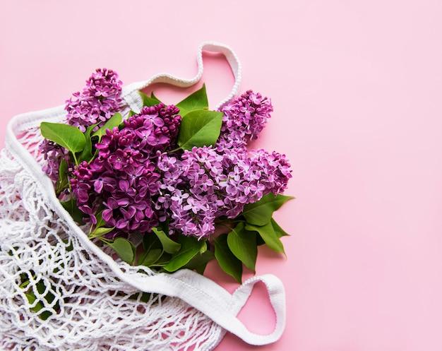 분홍색 배경에 재사용 가능한 쇼핑 에코 메쉬 가방에 라일락 꽃다발. 개념 플라스틱, 폐기물 제로. 공간 복사 인사말 카드, 엽서, 초대장에 대 한 상위 뷰 템플릿.