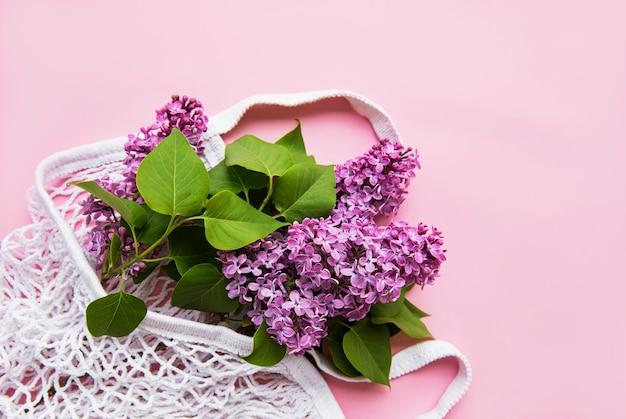 분홍색 표면에 재사용 가능한 쇼핑 에코 메쉬 가방에 라일락 꽃다발