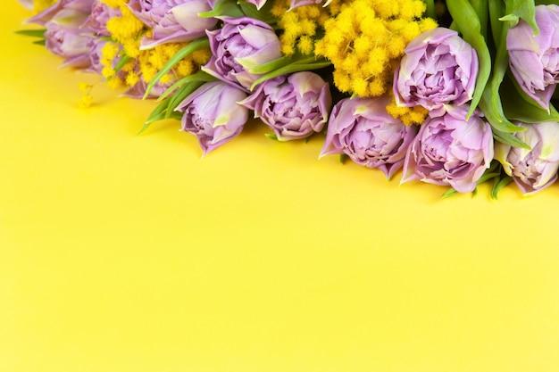黄色の壁、コピースペース、上面図、クローズアップを照らすライラックチューリップとミモザの花束。