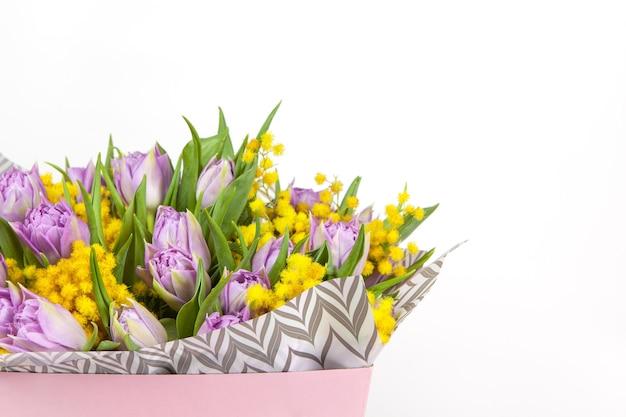 라일락 튤립과 흰색 배경에 분홍색 상자에 노란색 미모사의 꽃다발, 복사 공간, 측면보기