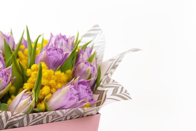 白地にピンクのボックスにライラックチューリップと黄色のミモザの花束