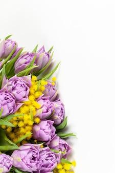 白い壁、コピースペース、側面図、クローズアップにライラックチューリップと黄色のミモザの花束。 Premium写真