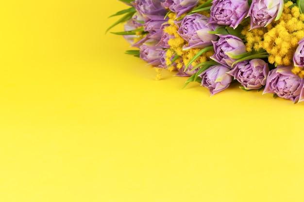 黄色の背景にライラックチューリップと黄色のミモザの花束