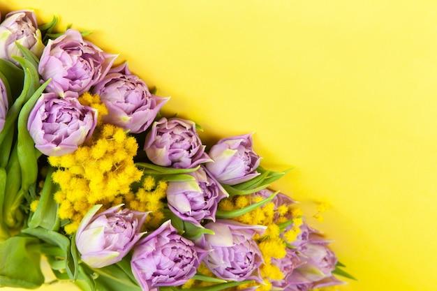 黄色の壁、コピースペース、上面図、クローズアップのライラックチューリップと黄色のミモザの花束。