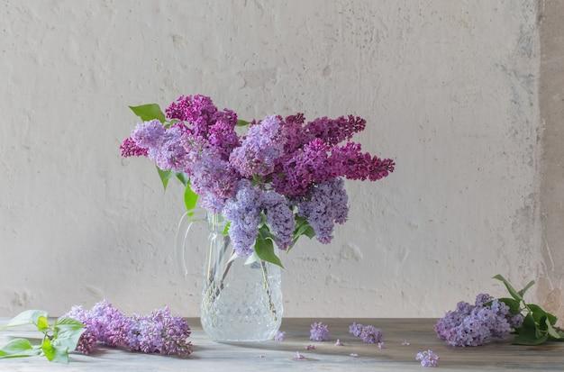 ガラスの水差しのライラックの花束