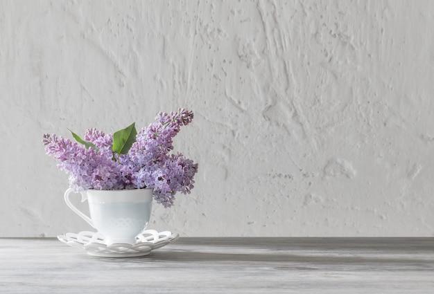 古い木製のテーブルの上のセラミックカップのライラックの花束
