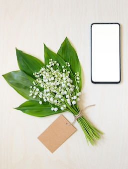 계곡의 백합과 스마트 폰의 꽃다발. 온라인 꽃 쇼핑 및 배달 개념.