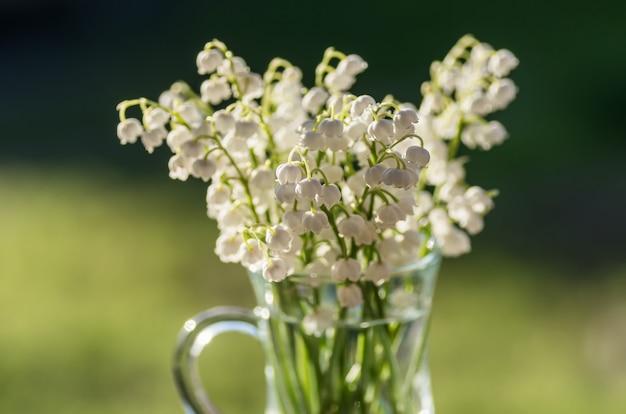 Букет из ландышей в стеклянной кружке. весенний цветочный фон.
