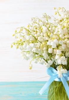 파란색과 흰색 나무 배경에 파란색 리본이 달린 꽃병에 계곡의 백합 꽃다발