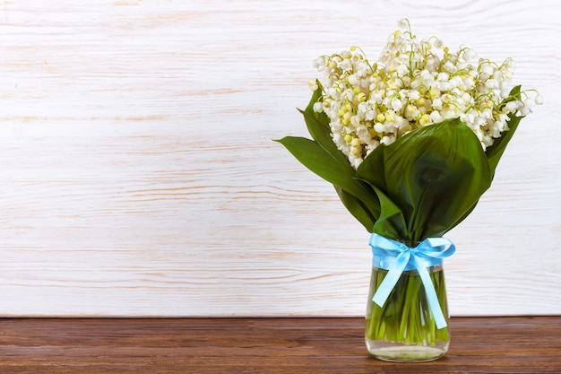 갈색과 흰색 나무 배경에 파란색 리본이 달린 꽃병에 계곡의 백합 꽃다발 프리미엄 사진