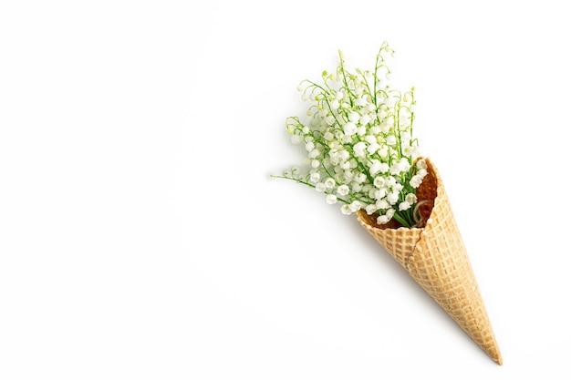 白い壁にワッフルコーンの谷のユリの花束。春の花とアイスクリームコーン。コピースペース、フラットレイ、上面図。花の壁。