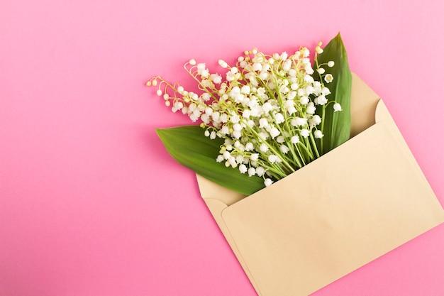 ピンクの表面の封筒にスズランの花束