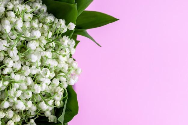 녹색 계곡의 백합 꽃다발 복사 공간이 부드러운 분홍색 벽에 나뭇잎