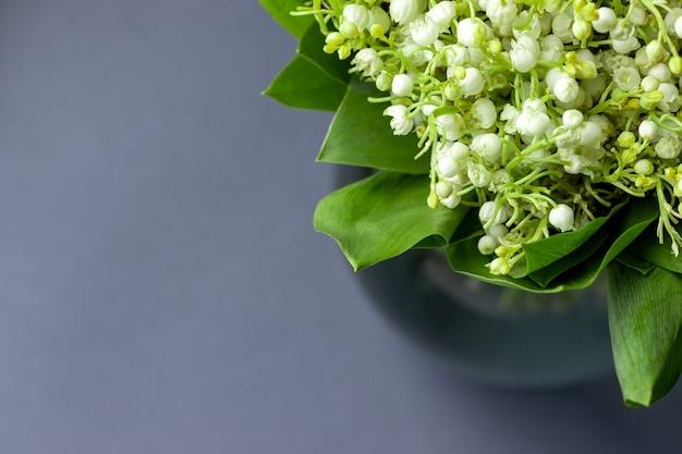 유리 꽃병에 잎에 계곡의 백합 꽃다발 프리미엄 사진