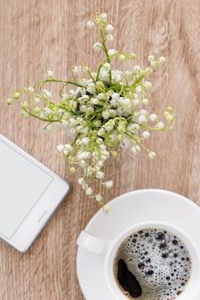 한 잔의 커피와 전화, 평면도와 테이블에 계곡의 백합 꽃다발