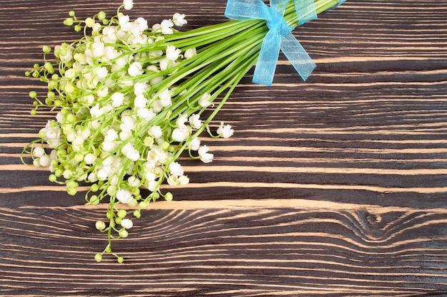茶色の木製の背景にスズランの花束。フラットレイ、テキスト用のスペースのある上面図。 Premium写真