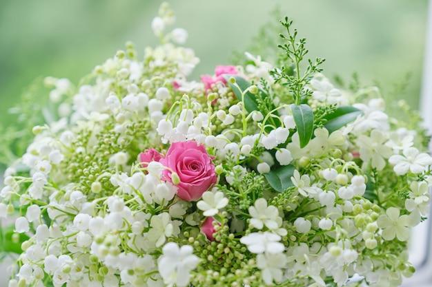谷間のユリの花束、ピンクのバラ、咲くガマズミ属の木