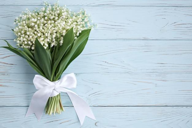 파란색 배경에 흰색 리본이 달린 은방울꽃 꽃다발