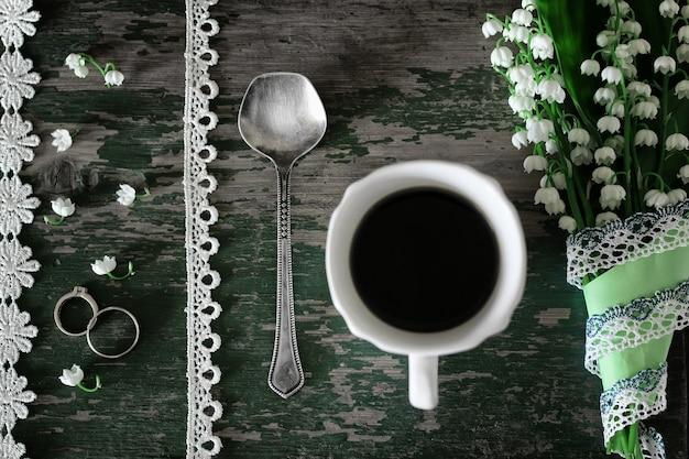 木製の背景と朝のコーヒーのユリの花束