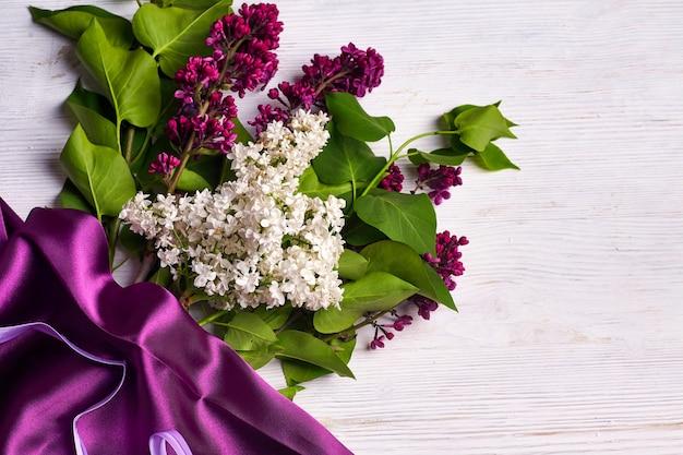 コピースペースと白い背景の上のライラックの花と紫色のカーテンの花束。