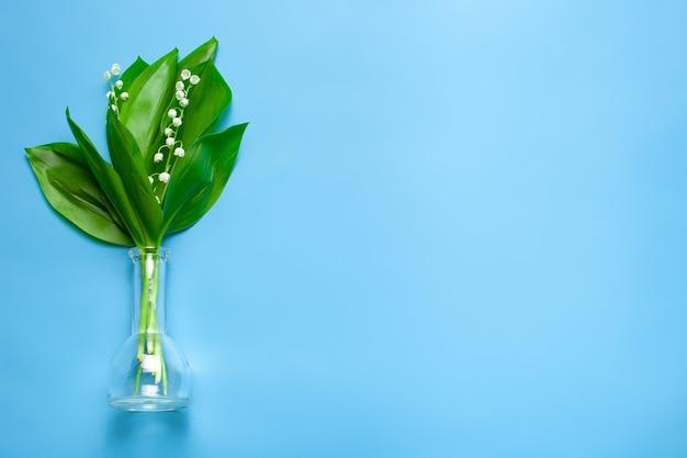 파란색 격리가 있는 왼쪽 상단 보기에 있는 투명한 유리 꽃병에 있는 은방울꽃 꽃다발...