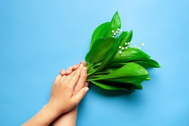 青い背景の結婚式やグリーティングカードの女性の手のひらの谷のリリーの花束