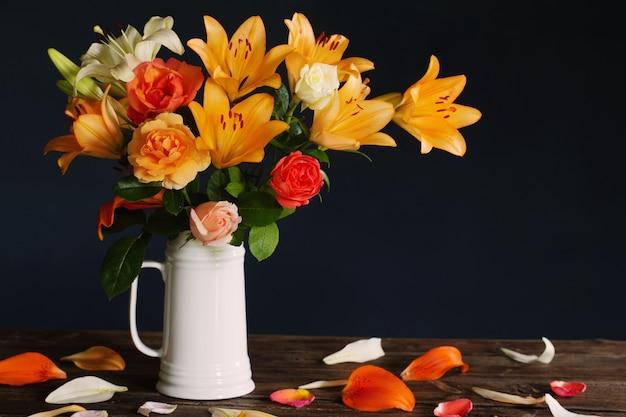 Букет цветов лилии в белом кувшине на темно-синем