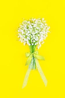 黄色の背景の上面図に弓とリボンとスズランの花の花束をクローズアップ
