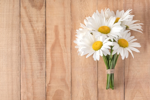 木製のテーブルフラットレイフリースペースに素敵なカモミールの花の花束