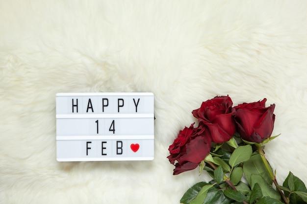 乳白色の毛皮のカーペットに栗色のバラの花束、バレンタインデーを意味するハッピー14febの碑文が付いたライトボックス。フラットレイ。上面図。