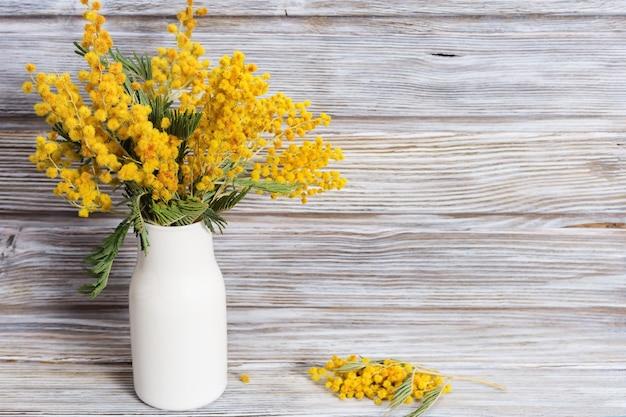 古い木の白いセラミック花瓶にミモザの花の花束