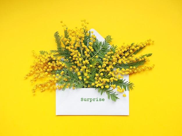 Букет цветов мимозы в белом конверте на желтом фоне
