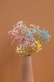 Букет разноцветных засушенных цветов в глиняной вазе ручной работы, стоящей на коричневой стене как часть интерьера домашней комнаты.