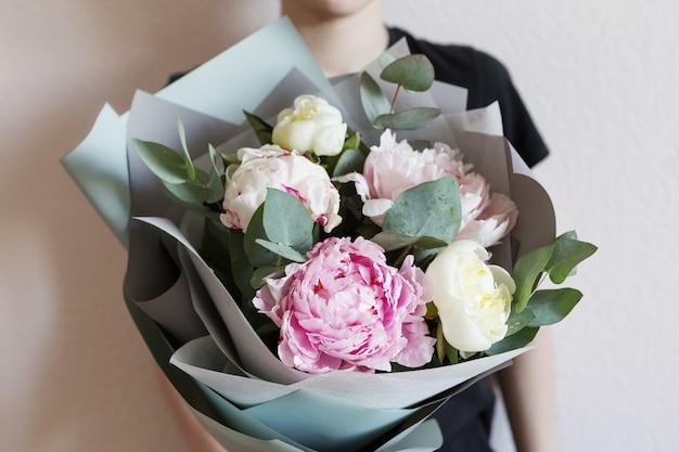 女性の手で灰色のクラフトペーパーでユーカリの枝と色とりどりのパステル牡丹の花束。 。