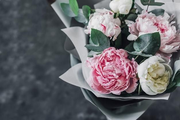 グレーのクラフトペーパーでユーカリの枝と色とりどりのパステル牡丹の花束。