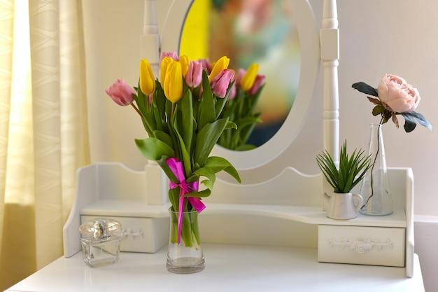 밝은 방에있는 흰색 화장대에 꽃병에 여러 가지 빛깔의 튤립 꽃다발