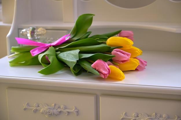 밝은 방에 흰색 테이블에 여러 가지 빛깔의 튤립 꽃다발