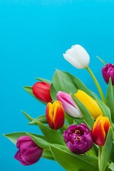 青色の背景に緑色の葉とさまざまな色の9つのチューリップの花束