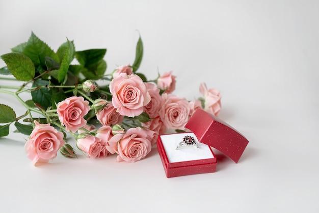 開いた赤い宝石箱に淡いピンクのバラと宝石で飾られた婚約指輪の花束。バレンタインデーを祝う