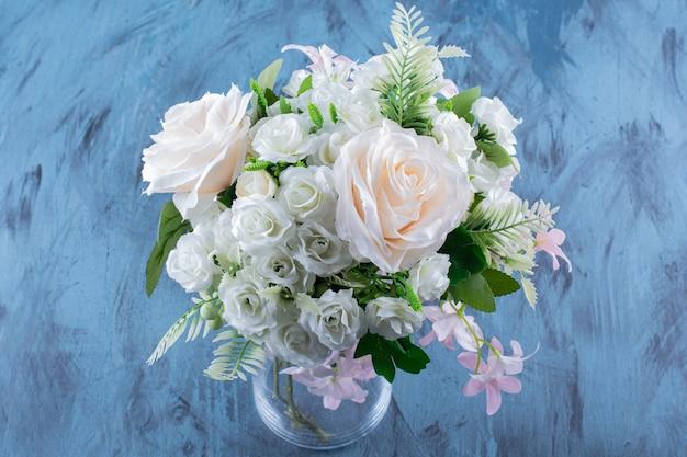 ガラスの花瓶に淡いバラの花の花束。