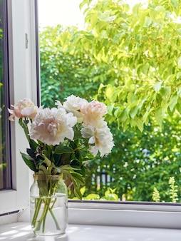 창턱에 꽃병에 모란 꽃다발.