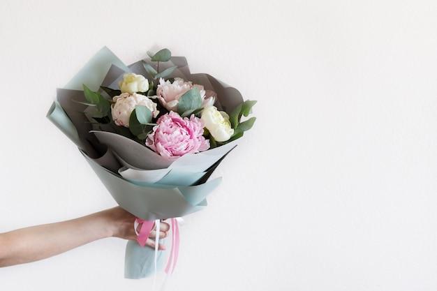 ユーカリの枝を手に持つ牡丹の花束