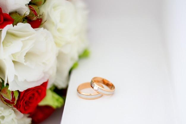 結婚指輪と牡丹のバラの花束