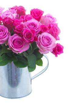 じょうろのピンクとマゼンタの新鮮なバラの花の花束は、白い背景で隔離を閉じることができます
