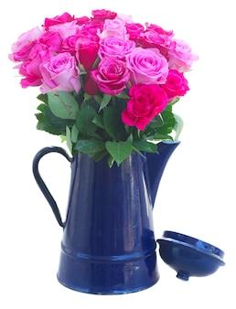 Букет из розовых и пурпурных свежих роз в синем горшке на белом фоне