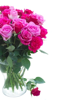 ピンクとマゼンタの新鮮なバラの花束は、白い背景で隔離のガラスの花瓶にクローズアップ