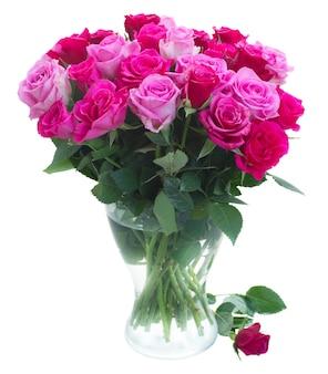 白い背景で隔離のガラスの花瓶のピンクとマゼンタの新鮮なバラの花束